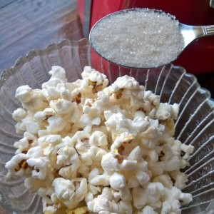 Adding pure cane sugar to freshly popped popcorn