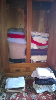 The AFTER Picture: The contents of the wardrobe are neatly folded and stacked, the piles in front are destined for the trash (L )and the Trinity Mission (L)